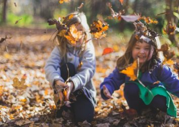 2 girls playing in a pile of fallen autumn leaves