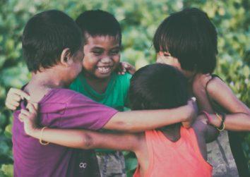 4 children huddled together in a circle